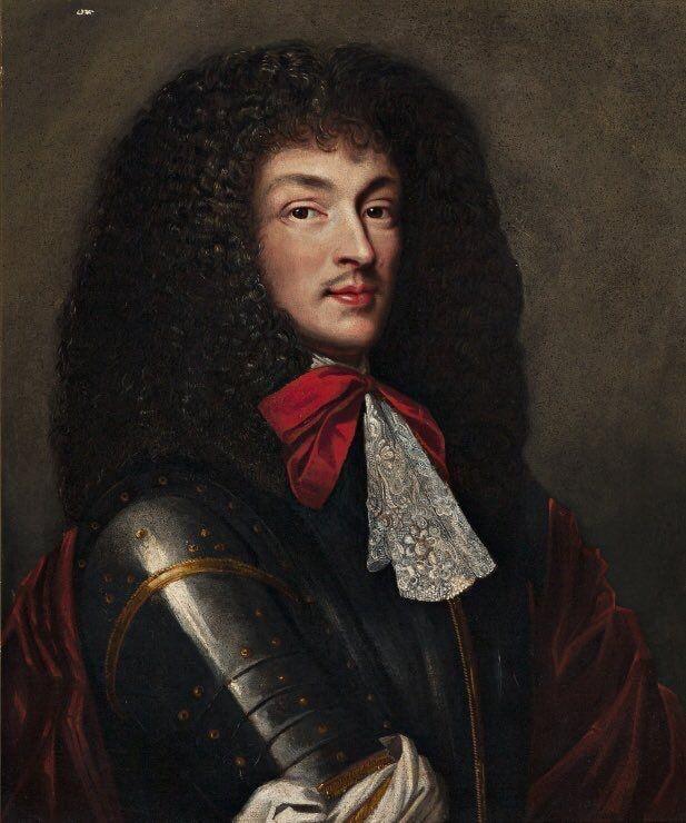 Luis XIV con peluca, lazo rojo, chorreras de encaje y los labios pintados.
